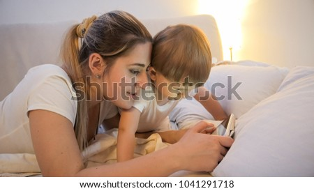 Portrait of mother with her toddler son watching cartoons on digital tablet in bed