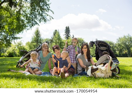 Portrait of mothers and children enjoying picnic in park - stock photo