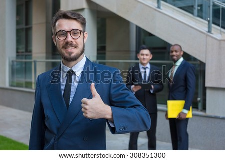 Portrait of multi ethnic business team holding their thumbs up. Three  man hand showing thumbs up against the backdrop of the city. The one man is European, other is Chinese and African-American.  - stock photo