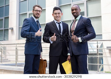 Portrait of multi ethnic business team holding their thumbs up. Three  men hands showing thumbs up against the backdrop of the city. The one man is European, other is Chinese and African-American.  - stock photo