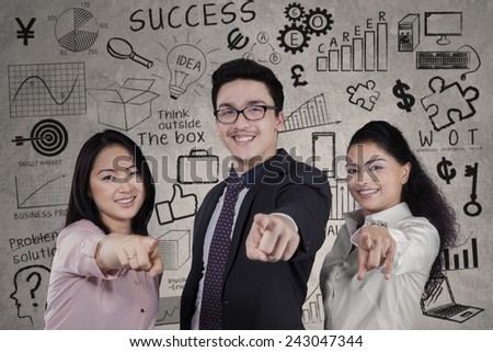 Portrait of multi ethnic business team pointing at camera in front of scribbles - stock photo