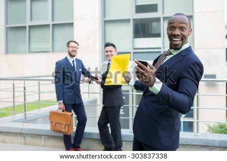 Portrait of multi ethnic business team. Three happy smiling men standing against the backdrop of the city. The one man is African-American, other is Chinese and European. concept of business success - stock photo