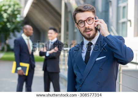 Portrait of multi ethnic business team.Three men standing against the background of city. The foreground of a European man  talking on the phone. Other men is Chinese and African-American.  - stock photo