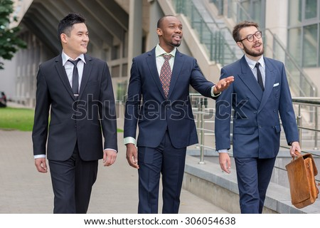 Portrait of multi ethnic business team.Three smiling men walking against the background of city. The one man is European, other is Chinese and African-American. - stock photo