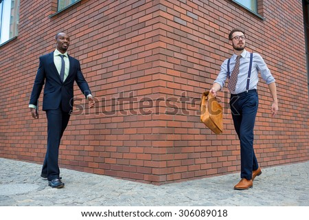 Portrait of multi ethnic business team. Two happy smiling men  walking towards each other against the backdrop of the city. The one man is African-American, other is European. concept of business - stock photo