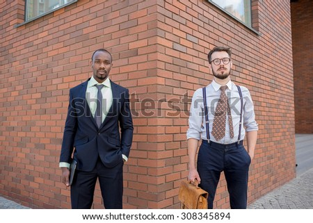 Portrait of multi ethnic business team. Two men standing against the backdrop of the city. The one man is African-American, other is European. concept of business success and old and new business - stock photo