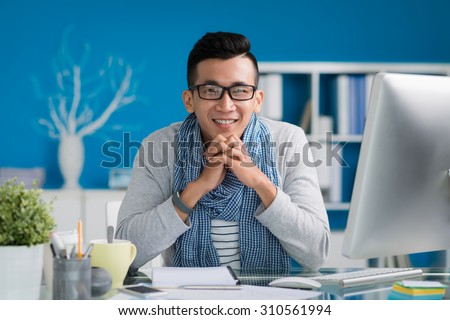 Portrait of multi-ethnic young businessman at his desk looking at the camera - stock photo