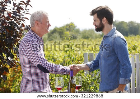 Portrait of multi generations winemakers standing at vineyard. Senior and young man working together at family business and shaking hands.