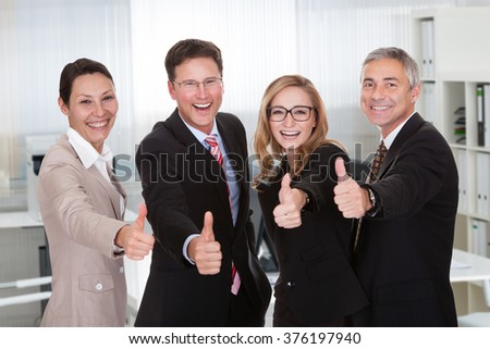 Portrait of multiethnic business people gesturing thumbs up while standing in office