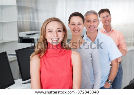 Portrait of multiethnic business people smiling while standing in row in office