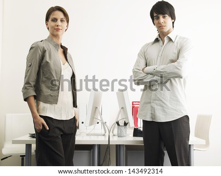 Portrait of multiethnic businessman and businesswoman standing at computer desks - stock photo