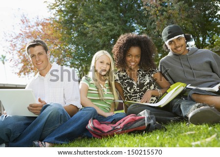 Portrait of multiethnic college friends studying in campus - stock photo