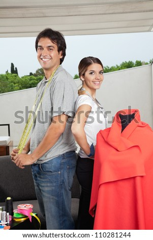 Portrait of multiethnic male and female fashion designers standing together beside mannequin - stock photo