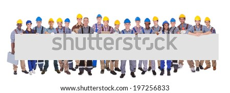 Portrait of multiethnic manual workers holding blank banner against white background