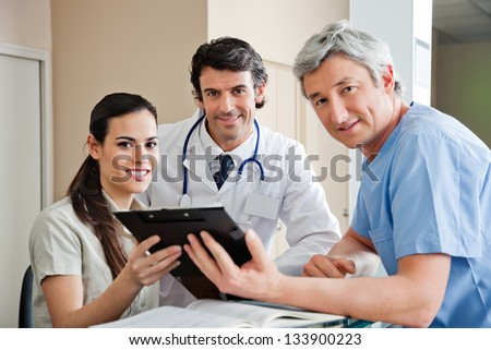 Portrait of multiethnic medical professionals smiling while standing at hospital reception