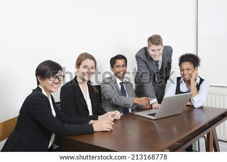 Portrait of multiethnic professionals using laptop at conference room - stock photo