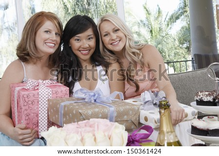 Portrait of multiethnic women with presents at wedding shower - stock photo
