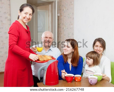 Portrait of multigeneration family having breakfast at home - stock photo