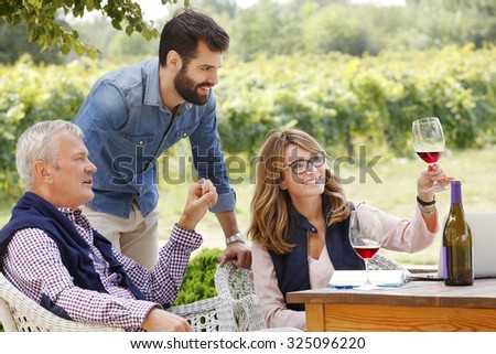 Portrait of multigenerational winemaker family working together. Senior winery owner and winemaker woman working on laptop and consulting with young sommelier while tasting red wine. Small business.  - stock photo