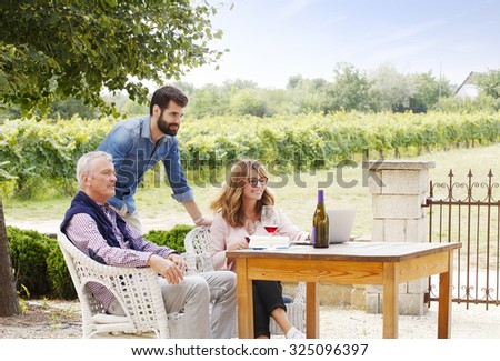 Portrait of multigenerational winemaker family working together. Senior winery owner and winemaker woman working on laptop and consulting with young sommelier while tasting red wine. Small business.
