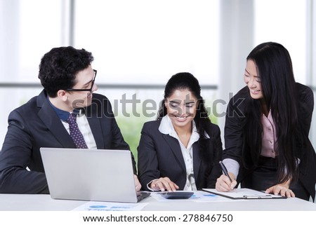 Portrait of multiracial business people working together with laptop, calculator, and documents - stock photo