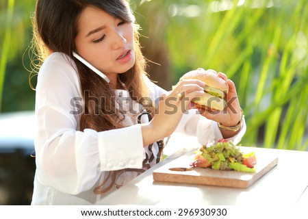 portrait of multitasking woman talking on the phone while eating burger - stock photo