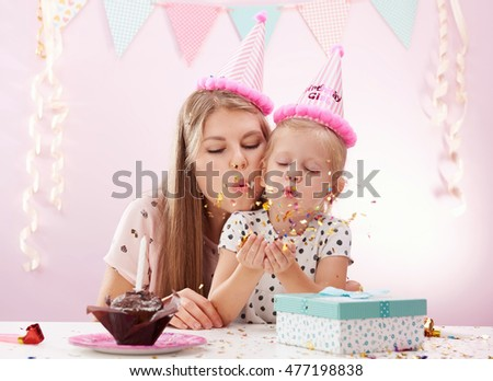 Portrait of mum and daughter blowing golden confetti celebrating birthday. Concept of holiday and fun.