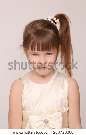 Portrait of mummy's little girl. Girl in white dress with a ponytail looking so serious. - stock photo
