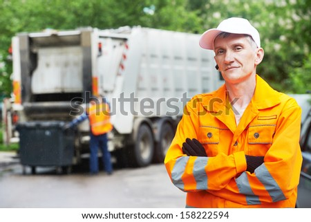 Portrait of municipal worker recycling garbage collector truck loading waste and trash bin - stock photo