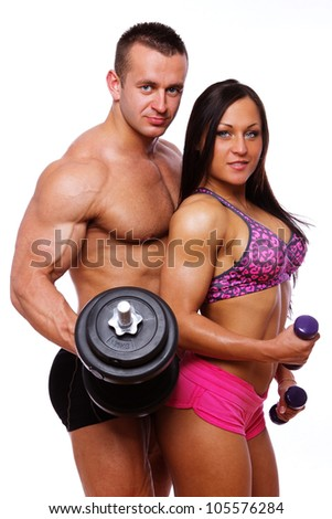 Portrait of muscle couple posing in studio with dumbbells - stock photo