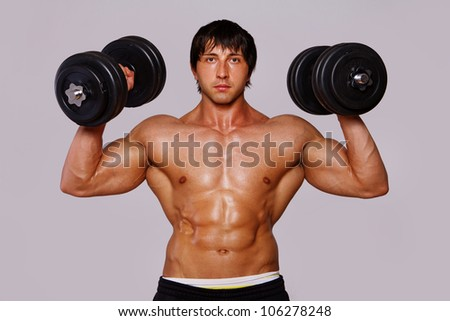 Portrait of muscle man doing exercises with dumbbells - stock photo