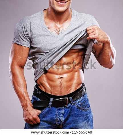 Portrait of muscle man posing in studio in grey t-shirt - stock photo