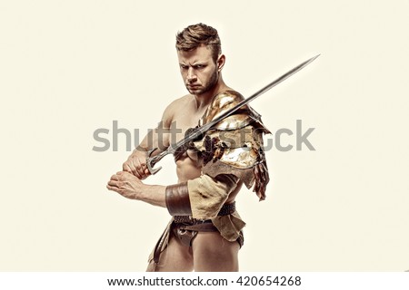 Portrait of muscular and strong gladiator in leather bagged clothes holding sword. Isolated. - stock photo