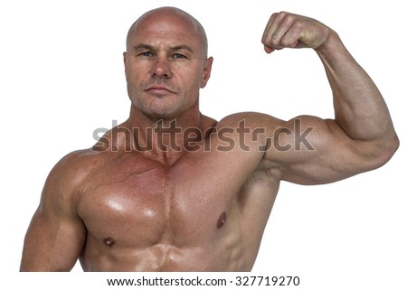 Portrait of muscular man flexing bicep against white background - stock photo