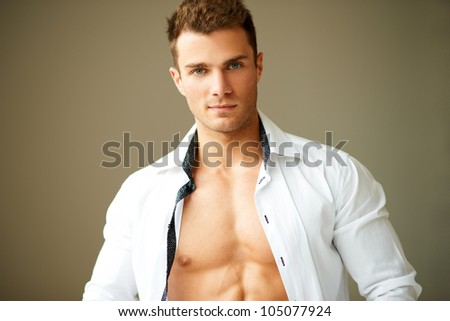 Portrait of muscular man posing in white shirt over brown background - stock photo