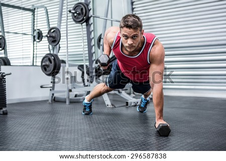 Portrait of muscular man using dumbbells in crossfit gym - stock photo