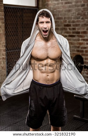 Portrait of muscular man wearing hood at the gym - stock photo