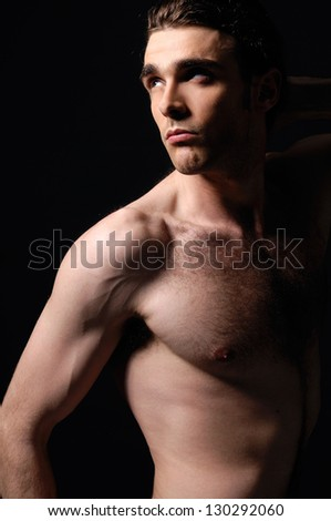 portrait of muscular young man against black - stock photo