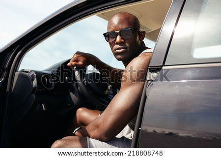 Portrait of muscular young man in car. African male model wearing sunglasses sitting on driver seat looking at camera.