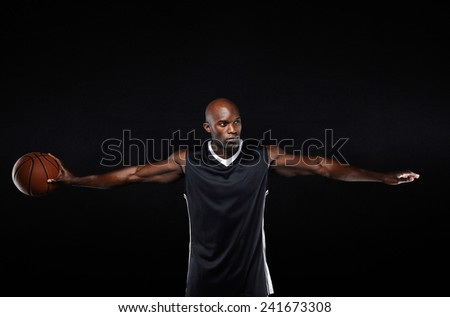 Portrait of muscular young man in sportswear holding a basketball standing with his arms outstretched looking away against black background. - stock photo
