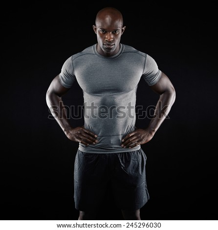 Portrait of muscular young man in sportswear standing with his hands on hips against black background. Strong african athlete. - stock photo