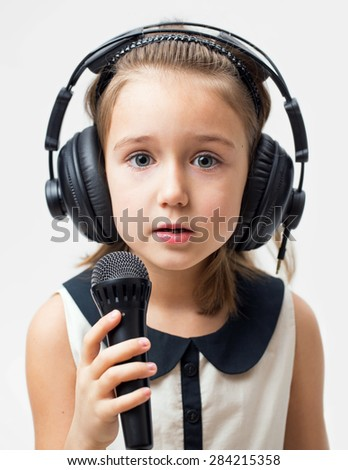 Portrait of music girl with  headphones and microphone