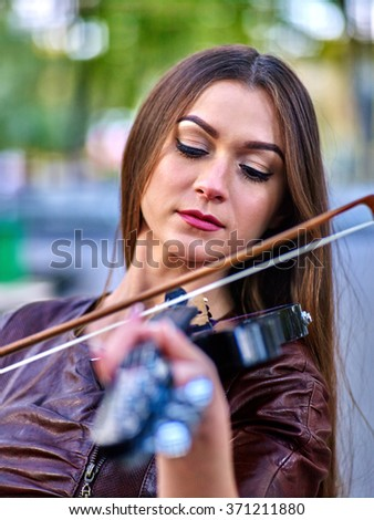 Portrait of music street performers girl violinist playing   outdoor.