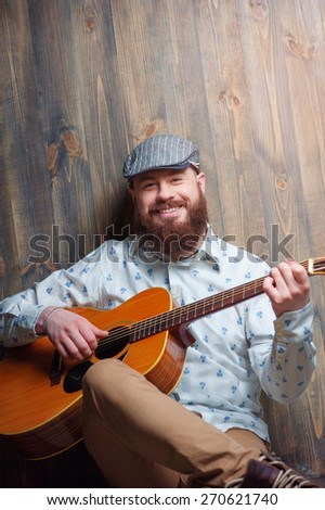 Portrait of musician. Handsome young bearded man sitting playing acoustic guitar over wooden background. - stock photo