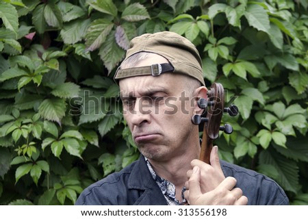 Portrait of musician with exhausted gaze, holding violin, lush foliage in the background - stock photo