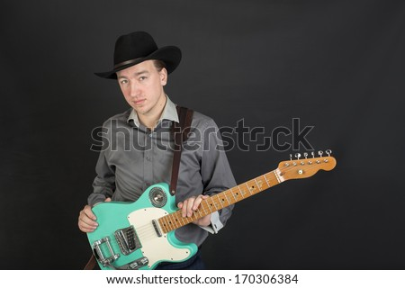 Portrait of musician with guitar on black background