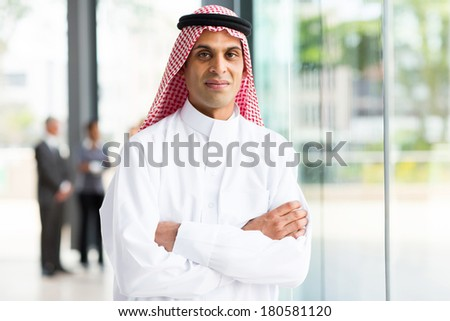 portrait of muslim businessman with arms crossed - stock photo