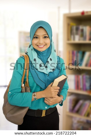 Portrait of Muslim student in the library - stock photo