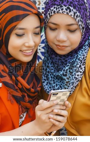 Portrait of Muslim student using smartphone outdoor  - stock photo