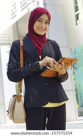 Portrait of Muslim woman wearing Hijab outdoor - stock photo